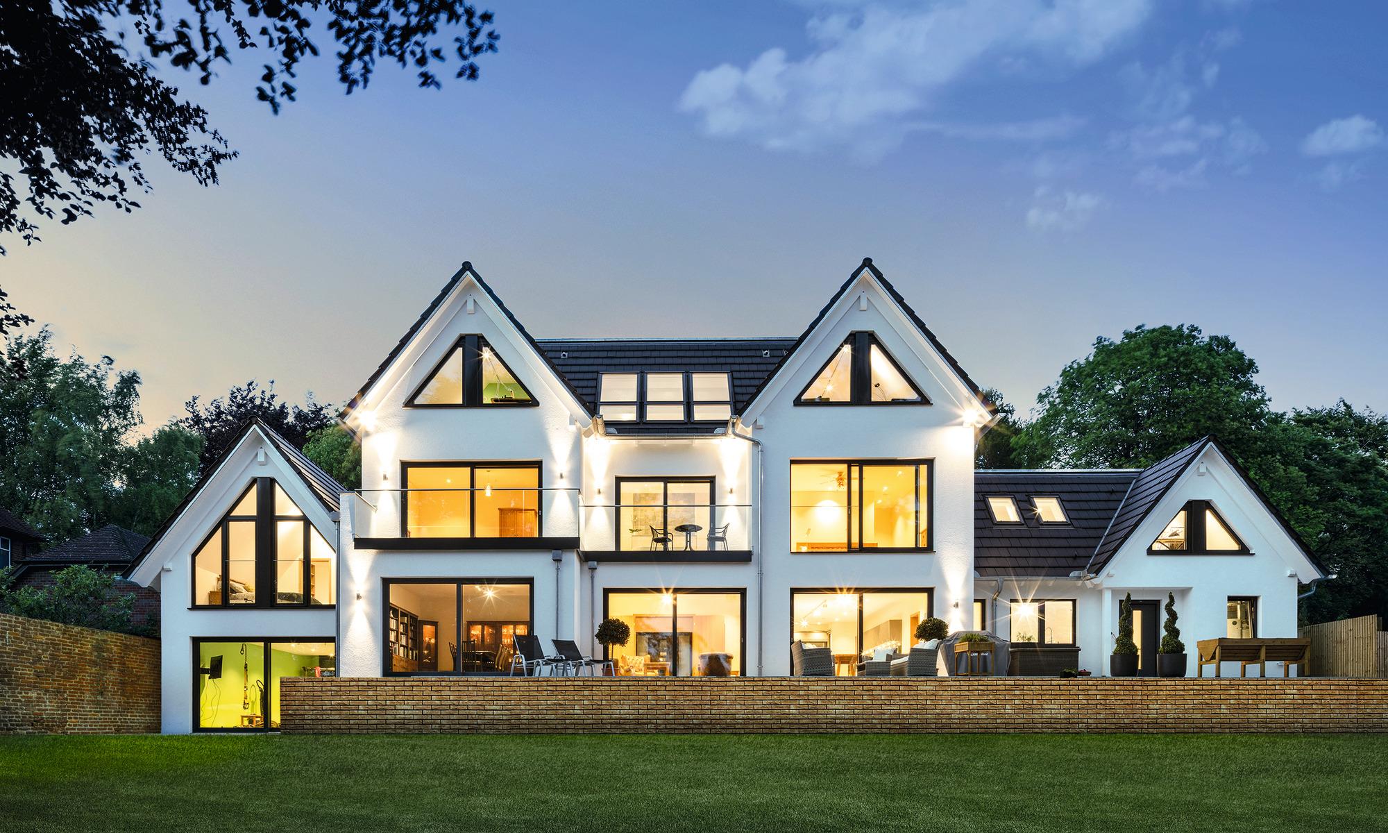 Haus mit großer Fensterfront in Abendstimmung