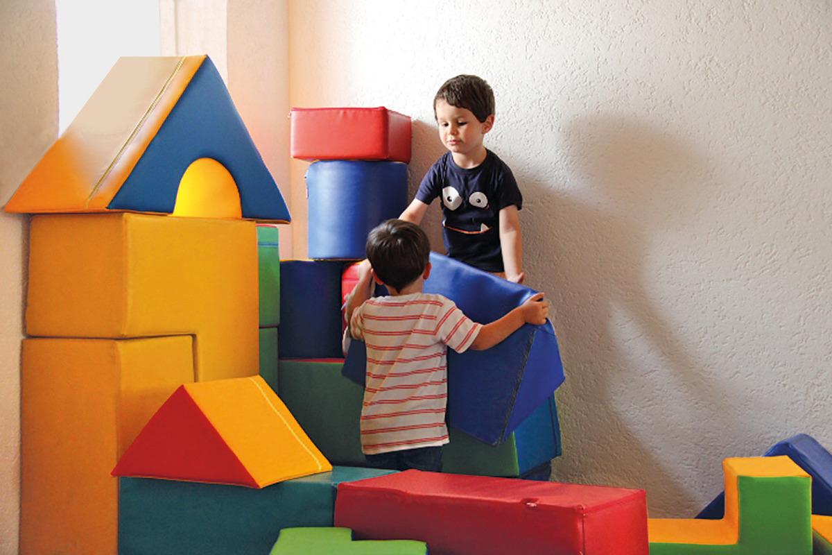 Kinder spielen mit Schaumstoff Bausteinen